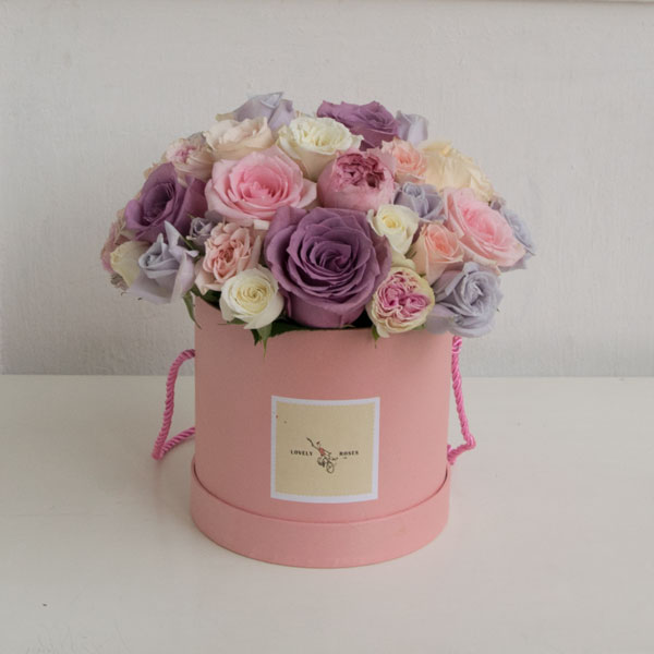 Different colored roses in a pink box
