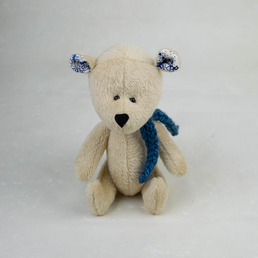 Small handmade teddy in a blue scarf